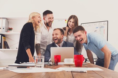Photo pour Happy business people laugh near laptop in the office. Successful corporate team of female and male coworkers joke and have fun together at work - image libre de droit