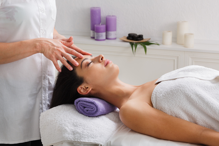 Head relaxing massage in spa. Female beautician doctor with patient in wellness center. Professional cosmetologist make procedure to beautiful indian girl in cosmetology cabinet or beauty parlor.
