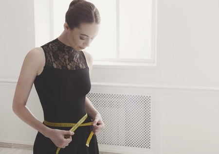 Ballet dancer looks at her perfect waist after diet. Beautiful graceful ballerine in black with measuring tape in light hall. Slimming and weight loss concept, copy space