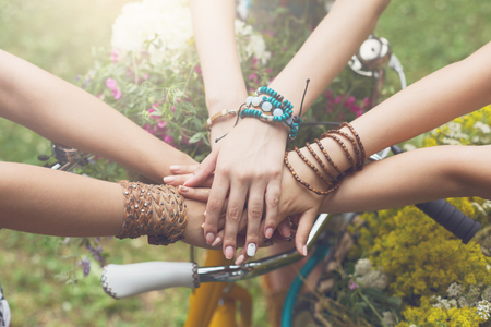 Photo for Girl Friendship. United hands of young females. Stylish girlfriends in boho hippie bracelets near bicycle handlebar, top view. Togetherness and support, youth fashion and active lesiure. - Royalty Free Image