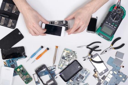 Photo pour Cell phone repair at service center, smartphone dissasembling and diagnostic, repairman workplace top view - image libre de droit