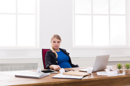 Pregnant woman working on laptop at office. Expectant businesswoman typing something on computer while sitting at her working place, copy space