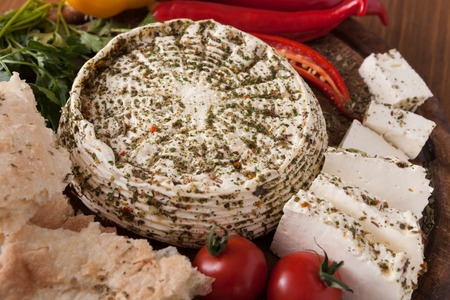 Homemade indian soft cheese paneer with herbs on wooden board with fresh vegetables and bread, close up