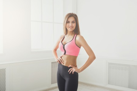 Photo for Beautiful fitness girl posing standing at window. Portrait of confident sporty woman with perfect body, healthy lifestyle and bodycare concept - Royalty Free Image