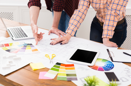 Unrecognizable professional designers team working on project, discussing functional space creation, decoration ideas, choosing color scheme