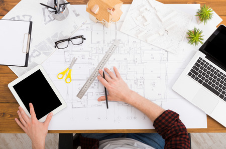 Foto de Architect drawing on architectural project. Top view on unrecognizable designer hands working with building blueprint, blank tablet and laptop screen, mockup - Imagen libre de derechos