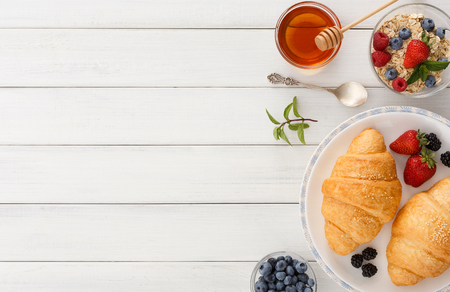 Photo pour Rich continental breakfast background. French crusty croissants, muesli, lots of sweet berries and honey for tasty morning meals. Delicious start of the day. Top view with copy space on wooden table - image libre de droit