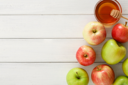 Photo pour Seasonal autumn background. Honey and lots of ripe apples on white wooden table with copy space, top view - image libre de droit