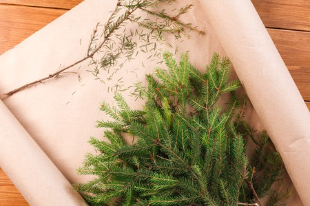 Prepare for christmas eve or other winter holidays. Fir tree branches in craft paper on wooden background., top view. Present packaging concept