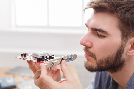 Photo pour Programmer studying broken video card in workshop. Young repairman examing computer motherboard to find crash, closeup - image libre de droit