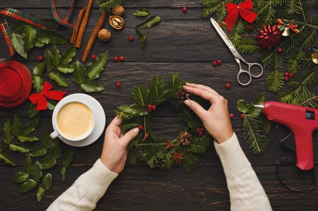 Foto de Creative leisure, tools and trinkets for xmas holiday decoration. Top view of dark wooden table background with female hands making wreath - Imagen libre de derechos