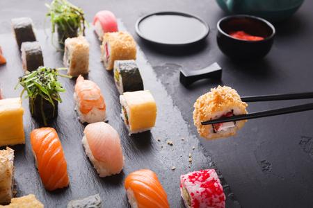 Foto de Eating sushi at restaurant. Chopstick taking roll with yellow tobiko, japanese cuisine, copy space - Imagen libre de derechos