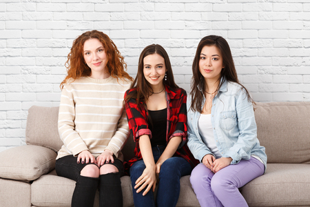 Three happy girls portrait sitting on sofa at home, white brick wall background with copy space. Friendship concept.