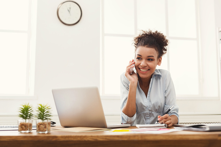 Photo pour Happy smiling african-american business woman at work talking on phone and taking notes, sitting at her working place in office, copy space - image libre de droit