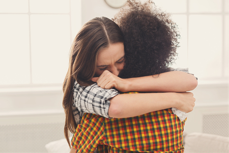 Foto de Woman hugging her depressed friend at home, closeup. Young girl supporting her crying girlfriend. Friendship consoling and care, copy space - Imagen libre de derechos