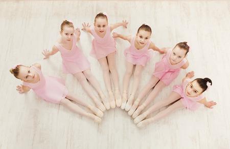 Photo pour Little ballerinas in ballet studio, top view. Group of girls practicing position sitting on floor, classical dance studio - image libre de droit