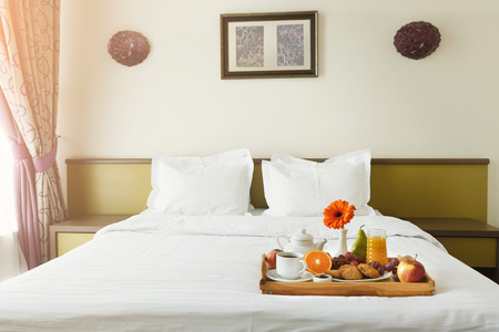 Foto de Breakfast served in bed on wooden tray with tea, juice, cookies, fruit and bright gerbera. Hotel room service, relax concept, copy space - Imagen libre de derechos