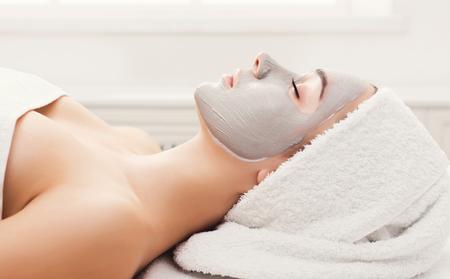 Foto de Face mask, spa beauty treatment. Woman applying facial clay mask at spa salon, skincare, side vies - Imagen libre de derechos