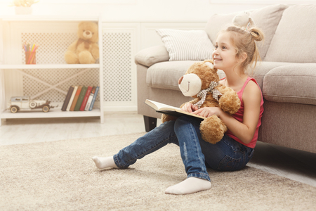 Photo pour Cute happy little casual girl embracing teddy bear and reading book. Pretty kid at home, sitting on the floor near sofa with her favorite toy, copy space - image libre de droit