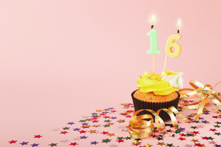 16th birthday cupcake with candles, sprinkles and ribbon on pink background. Card mockup, copy space. Birthday party and sweet sixteen concept