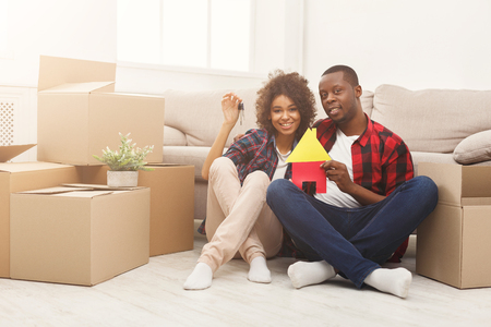 Photo pour Happy african-american family couple with house and key symbols. Sitting on floor against near storage boxes at new apartment. Moving and real estate concept, copy space, isolated - image libre de droit