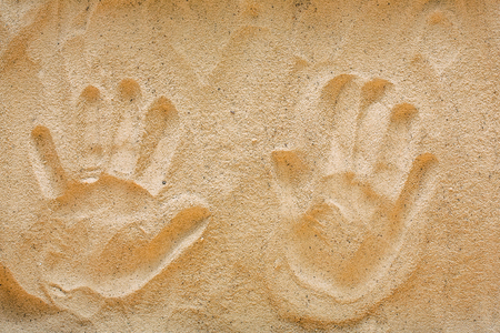 Two handprints on beach sand, top view. Creative textured background. Love and romance concept, copy space