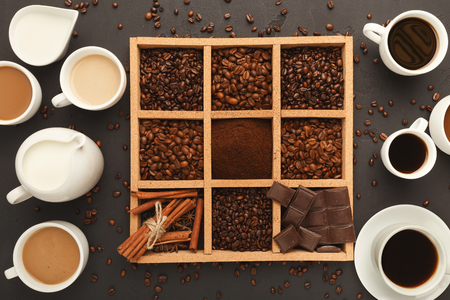 Assorted ground coffee and roasted beans, spices and chocolate in wooden square frame and various coffee cups on gray textured slate, top view, copy space. Template design for avertizing of cafeの写真素材