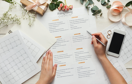 Foto de Wedding background with checklist and calendar. Female hands arranging marriage, filling in planners on white wooden table with lots of tender bridal stuff, top view - Imagen libre de derechos