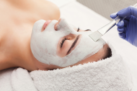 Face mask, spa beauty treatment, skincare. Woman getting facial nourishing mask by beautician at spa salon, closeup