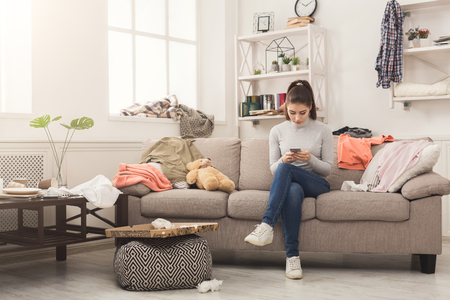 Photo pour Desperate helpless woman sitting on sofa in messy living room. and chatting on mobile, surrounded by many stack of clothes. Disorder and mess at home, copy space - image libre de droit