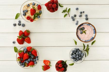 Healthy breakfast background. Light greek yogurt, muesli, fresh strawberries, raspberries, blueberries and blackberries frame on white wood with copy space. Detox and eating right concept, top view