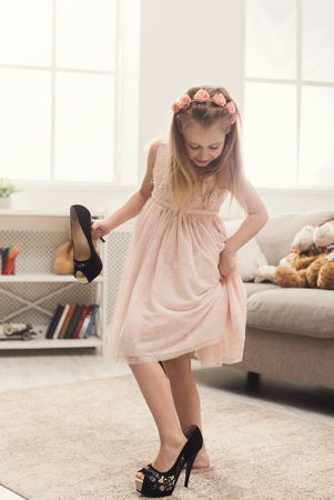 Foto de Pretty little girl in moms shoes. Small fashionista trying on high heels at home, copy space - Imagen libre de derechos