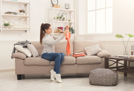 Photo pour Woman folding clean t-shirts, sitting on sofa at home. Young girl tidying up clothes after laundry or shopping, copy space - image libre de droit