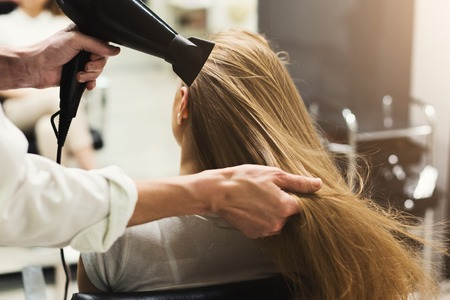 Stylist making hairstyle using hair dryer, blowing on wet customer hair at beauty salon, copy space
