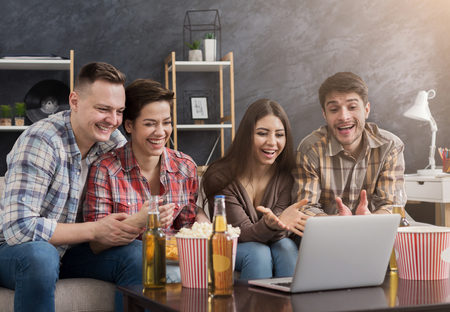 Photo pour Happy friends sitting on sofa and watching comedy movie on laptop at home - image libre de droit