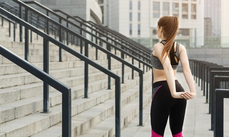 Unrecognizable woman doing stretching exercises on stadium stairsの写真素材