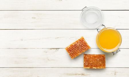 Jar full of fresh honey and honeycombs on white wooden table, top view, copy spaceの写真素材