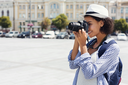 Photo pour African-american woman photographing with camera on vacation in city - image libre de droit