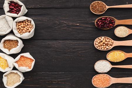 Foto de Various grains in cloth bags and spoons on wooden background, top view, copy space - Imagen libre de derechos