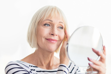 Photo pour Senior woman touching her soft face skin, looking in mirror at home - image libre de droit