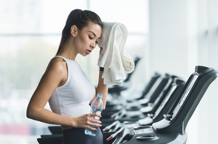 Photo pour Woman tired and having rest after running on treadmill in modern gym - image libre de droit