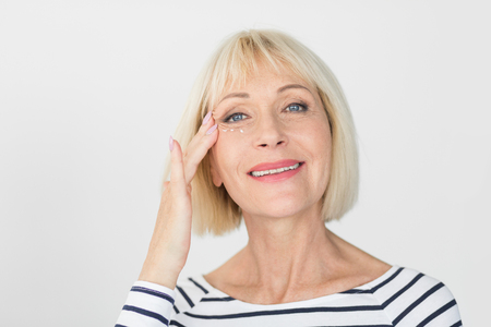 Beautiful woman applying anti-wrinkle cream, looking at camera over light background