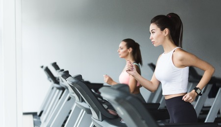 Foto de Fit women doing cardio workout, running on treadmill in gym, copy space - Imagen libre de derechos