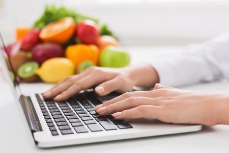 Foto de Healthy eating and food coach concept. Nutritionist consultation online, dietitian typing treatment to patient via internet, copy space - Imagen libre de derechos