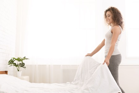 Photo pour Young woman making bed and organizing room in morning, copy space - image libre de droit