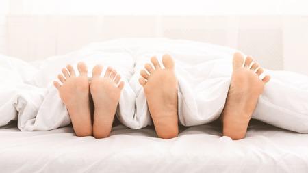 Foto de Bare feet of couple in bed. Loving couple lying under white blanket, panorama, copy space - Imagen libre de derechos