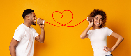 Love message. Lovely african-american couple talking on a tin phone, orange background, panorama