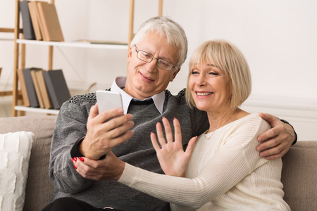 Photo pour Senior couple making video call from smartphone, having rest at home - image libre de droit