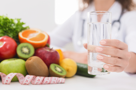 Photo pour Detox and cleansing concept. Doctor nutritionist holding glass of water at her office, free space - image libre de droit