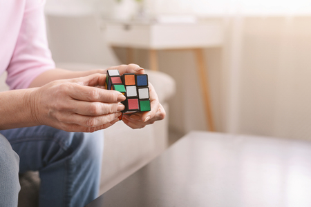 Photo pour Kharkiv, Ukraine - January 14, 2019: Old woman holding Rubik's cube and playing with it at home, Rubik's cube invented by Hungarian architect Erno Rubik in 1974, free space - image libre de droit
